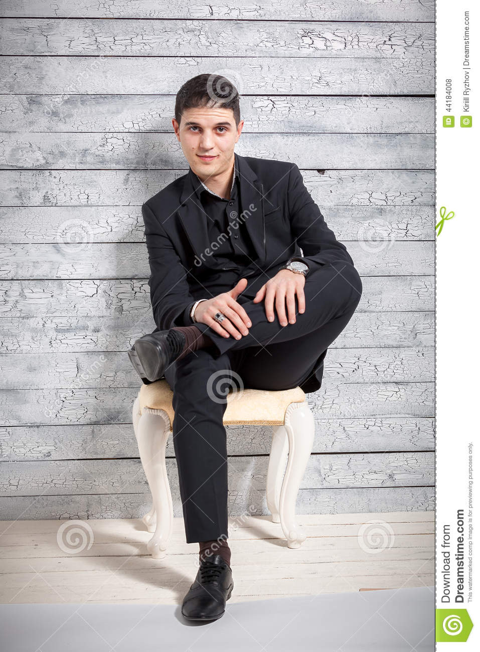 Man In Suit Sitting On Chair With Legs Crossed At Studio