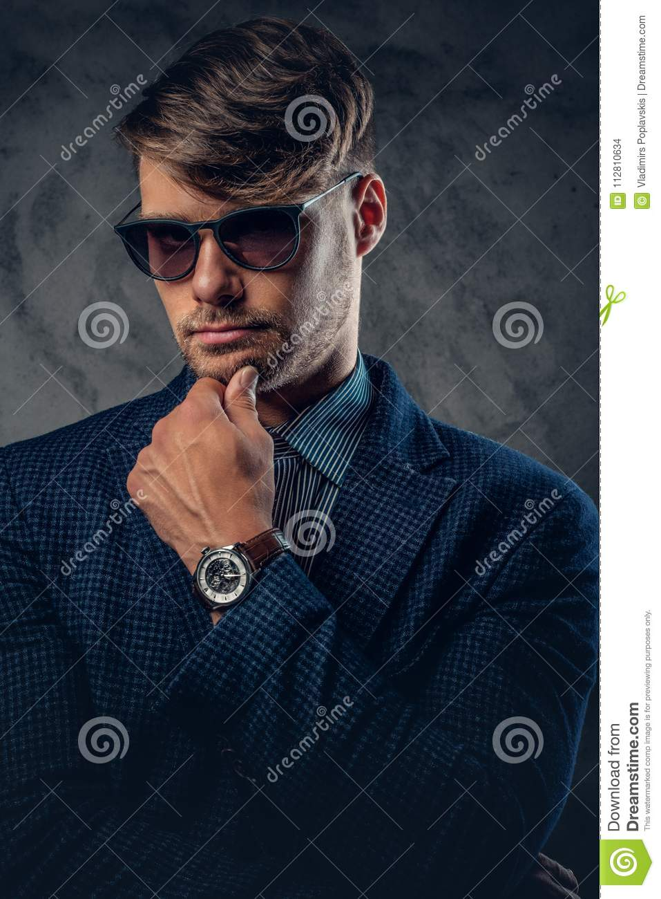 304423e7d1a0 A Man In A Suit And Sunglasses On Grey Background. Stock Photo ...