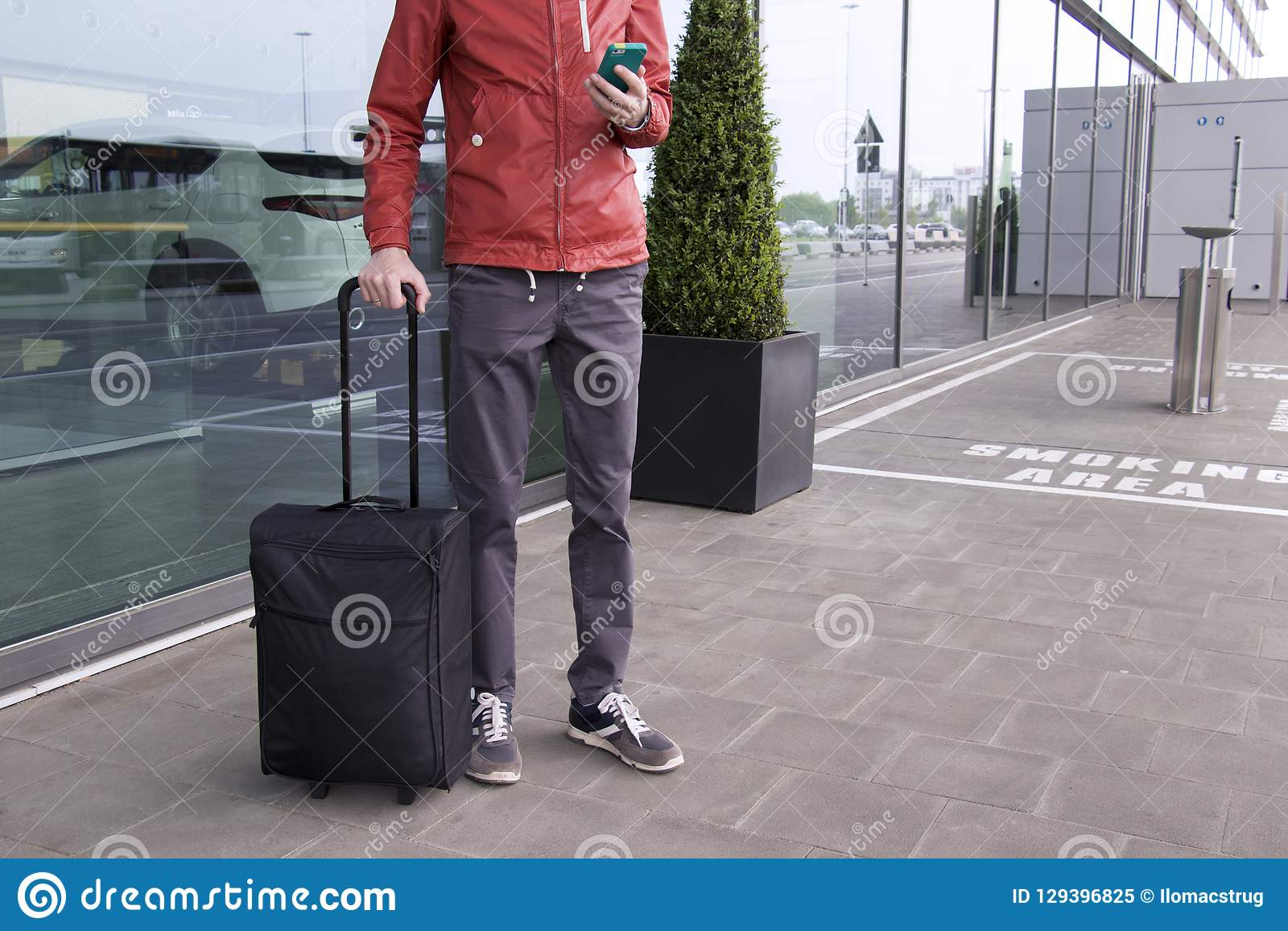 A man with suitcase and mobile phone near of airport.