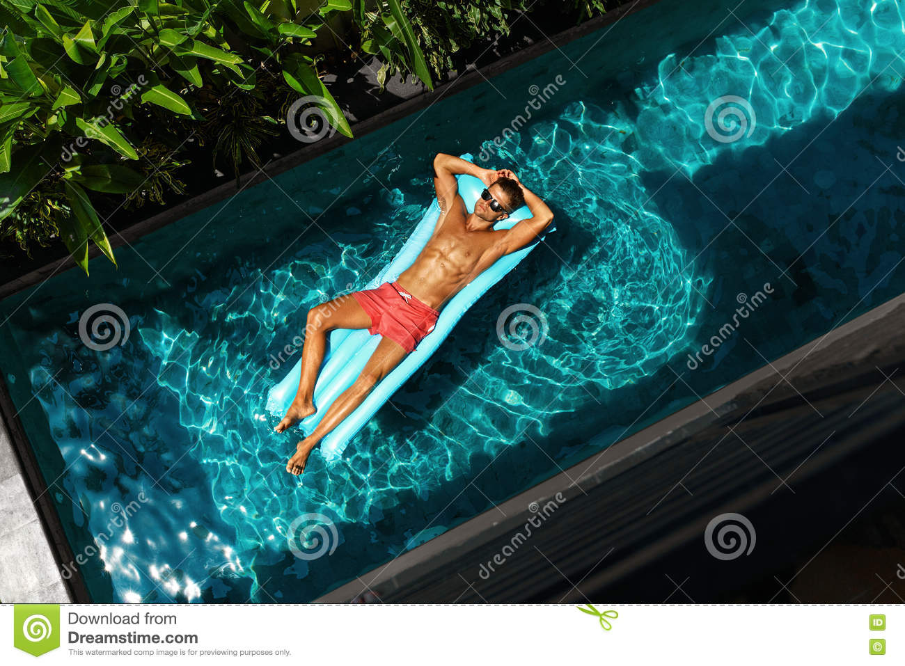 Man On Summer Vacation. Male Model Tanning In Swimming Pool