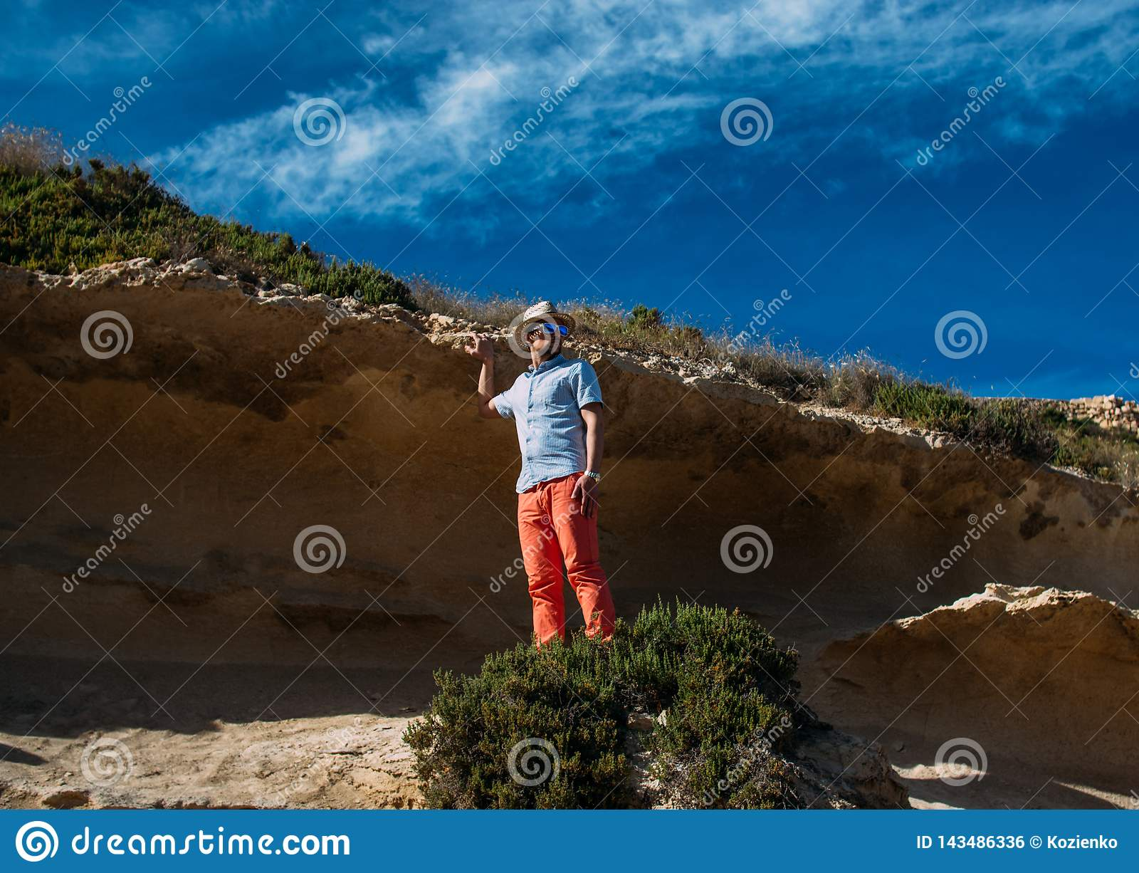 Man in sunglasses and red trousers staying in the hills