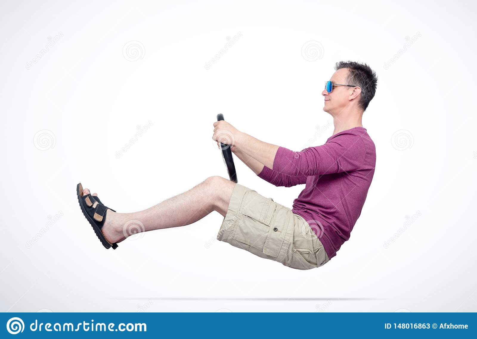 Man in sunglasses, shorts, red t-shirt and sandals drives a car with a steering wheel, on light background. Auto driver concept