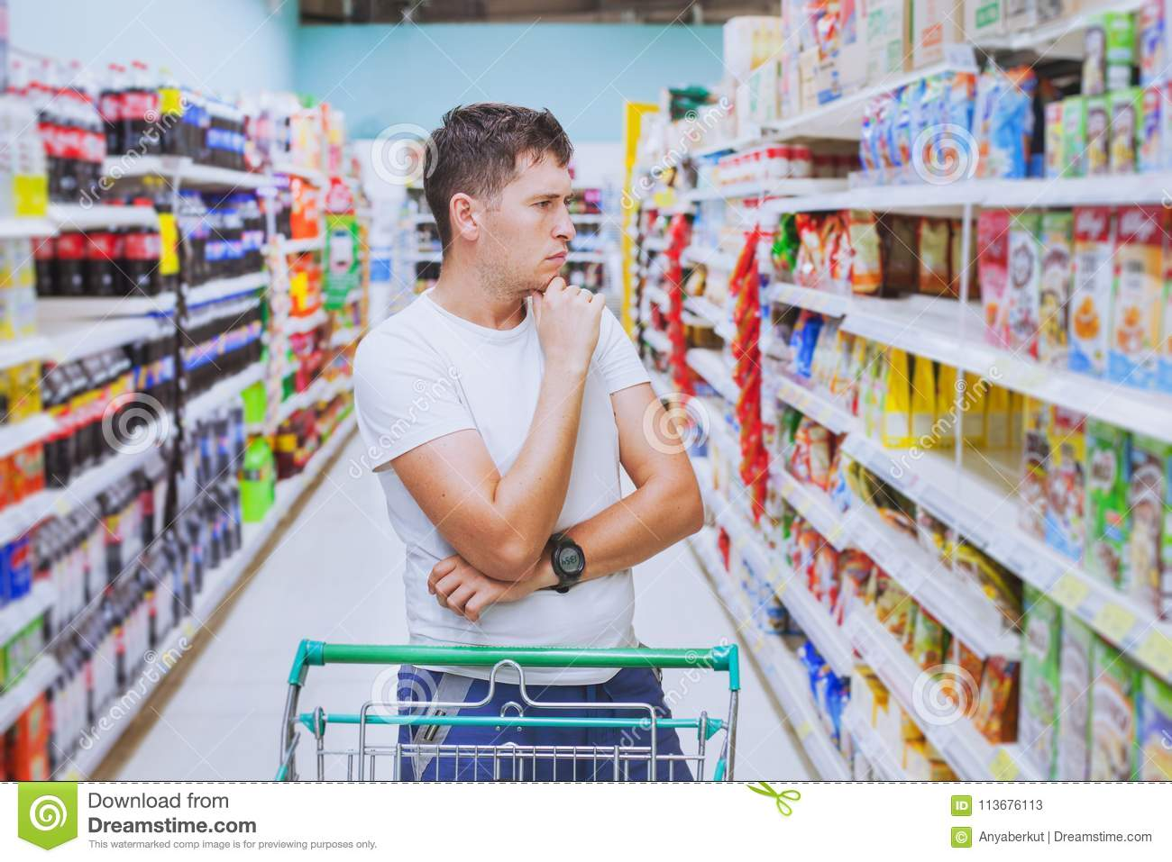 Man in the supermarket, customer thinking, choose what to buy