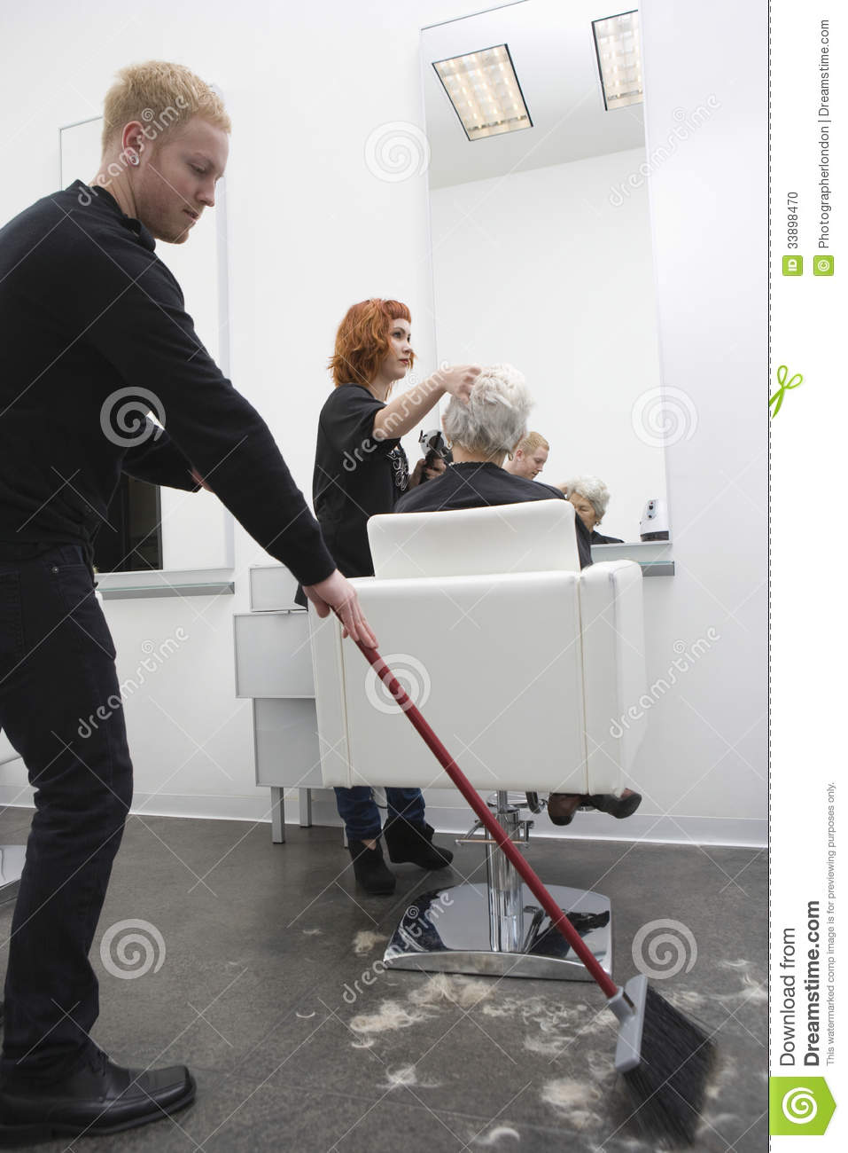 man sweeping while hairdresser giving haircut to senior woman stock photo