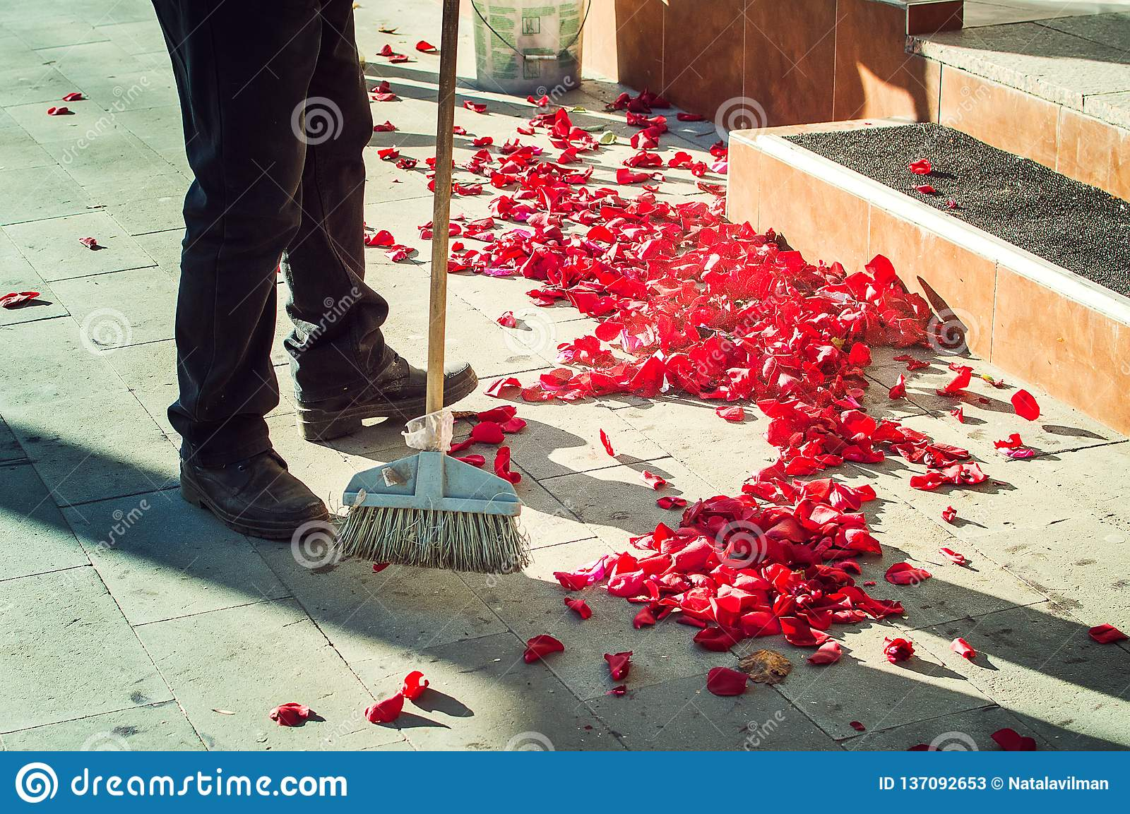 A man sweeps rose petals on the street after the wedding ceremony