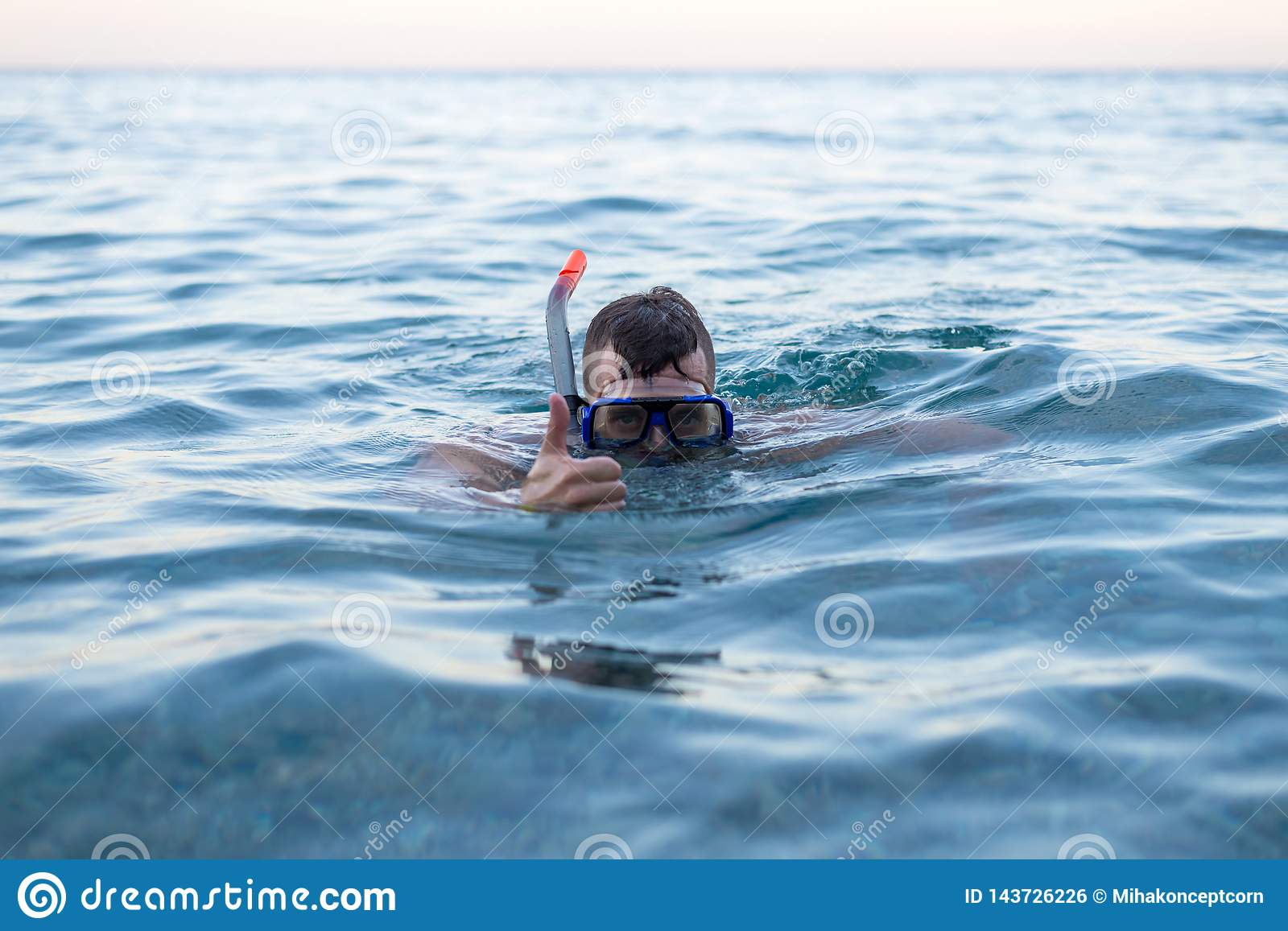 Man swimming in a mask for diving and showing a sign approx