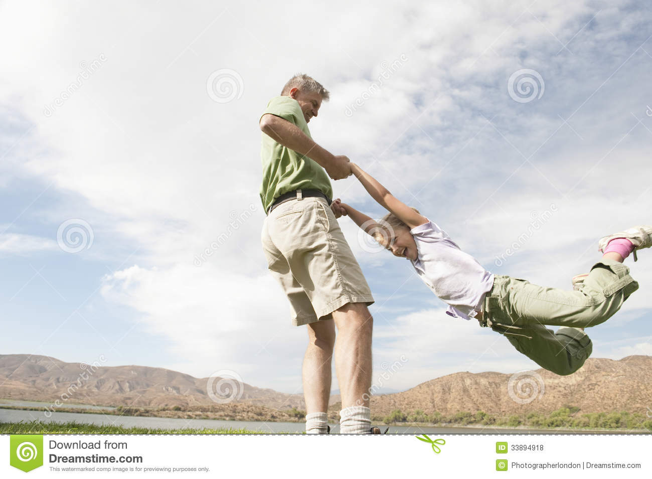 Low angle view of a men swinging his daughter by the hands against sky