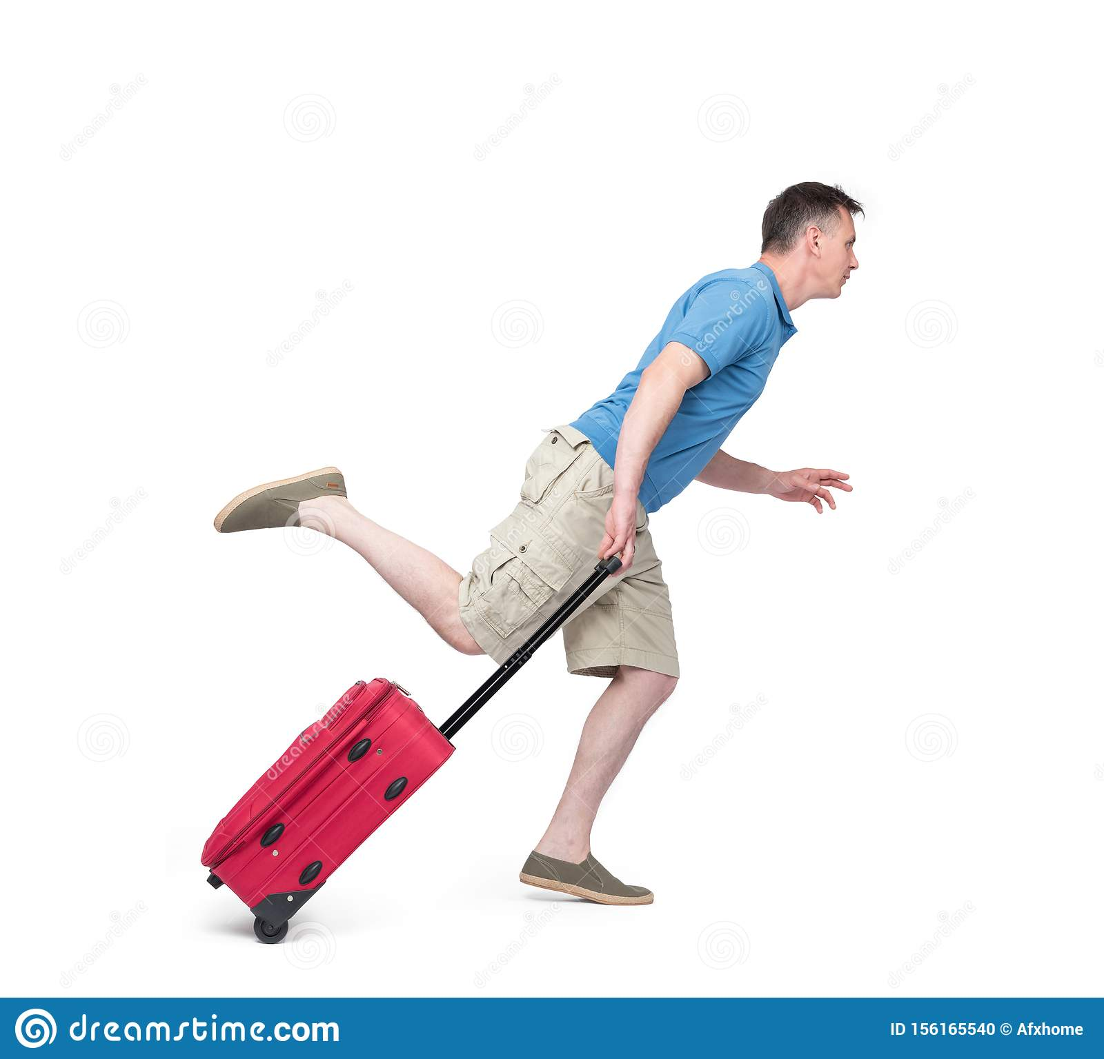 Man in a T-shirt, shorts and with a red suitcase hurries, runs. Isolated on white background. Late passenger concept
