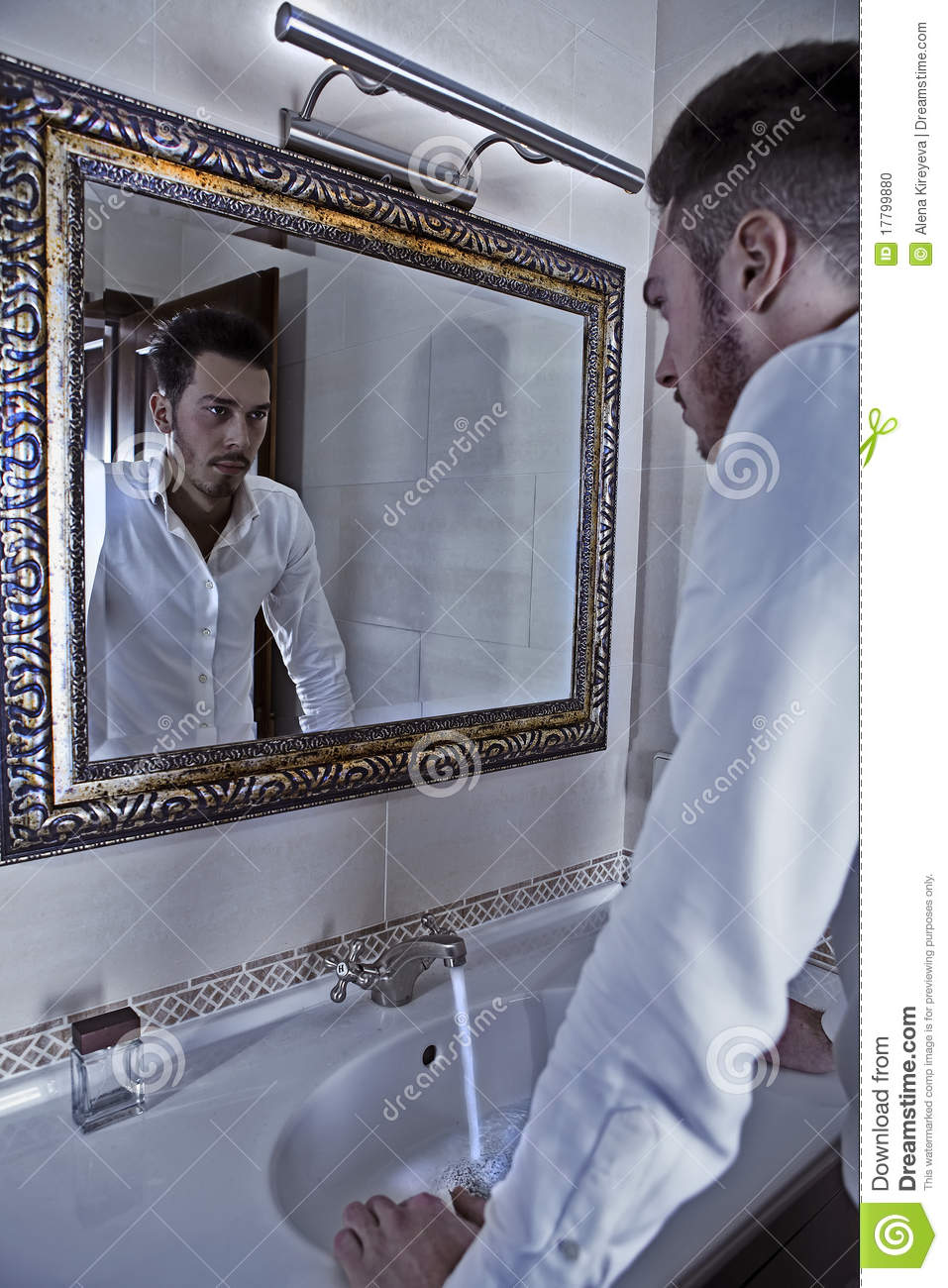 Man takes a look at himself in the mirror stock photo for Mirror that look