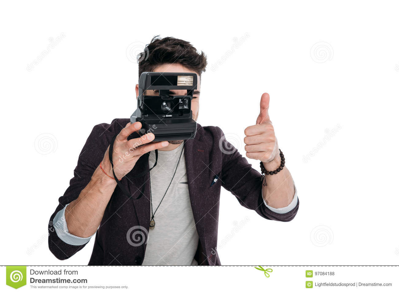 Man taking photo with polaroid camera and showing thumb up