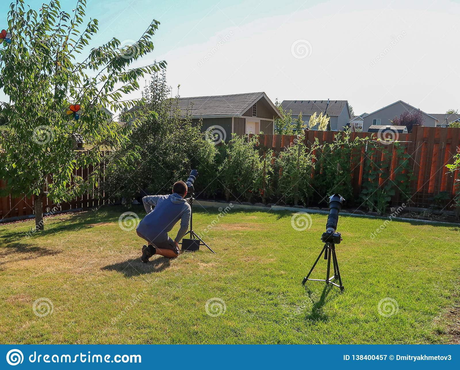 A man taking pictures of a total solar eclipse on a backyard of house