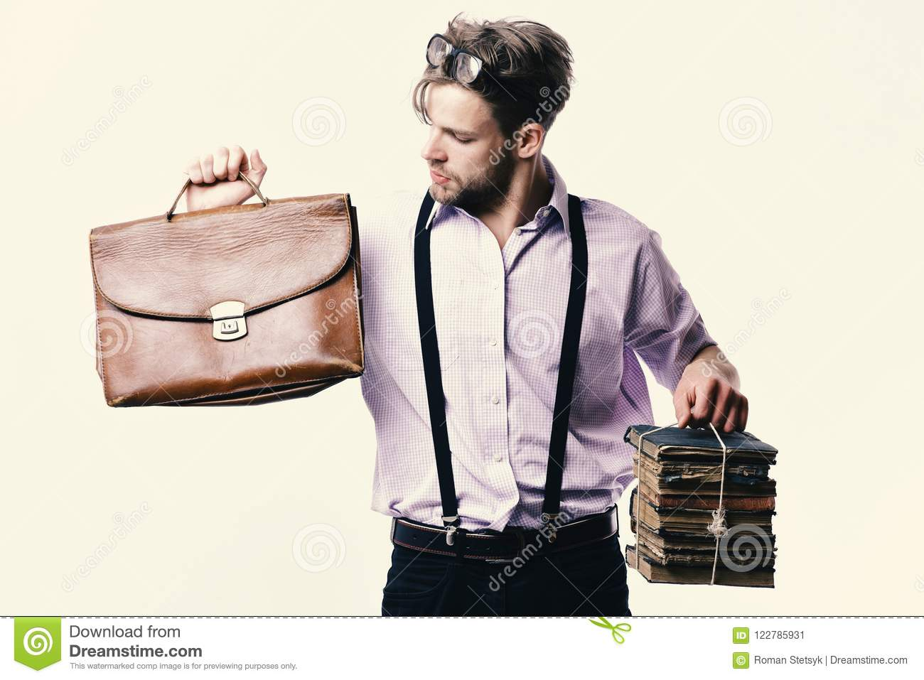 Man or teacher with bristle, glasses and curious face. Nerd or bookworm wearing suspenders. Man with briefcase