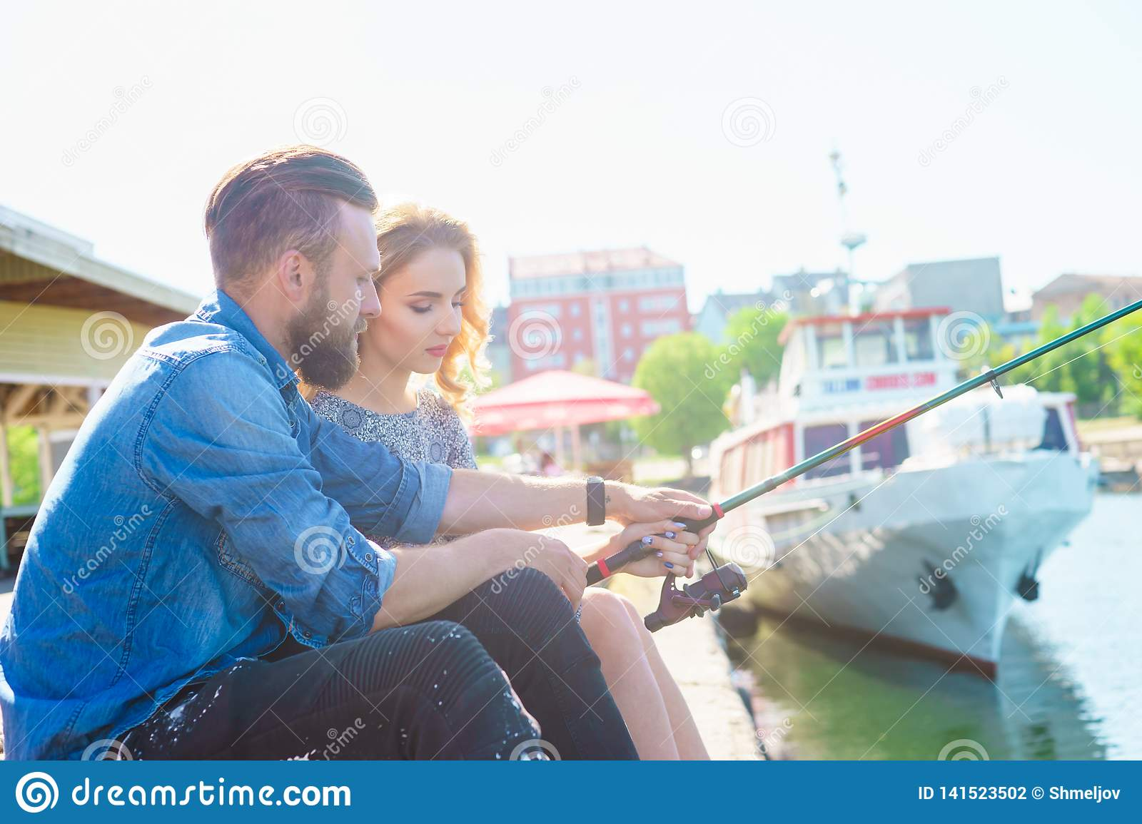 Man teaching his girlfriend to fishing. Date, love and hobby concept.