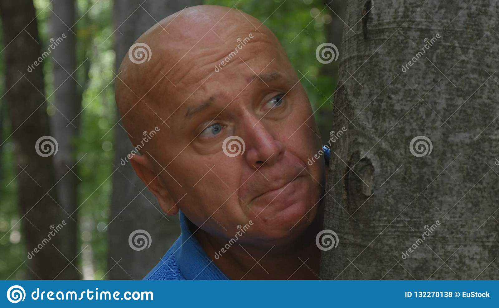 Terrified Man Is Hiding After a Tree in the Forest