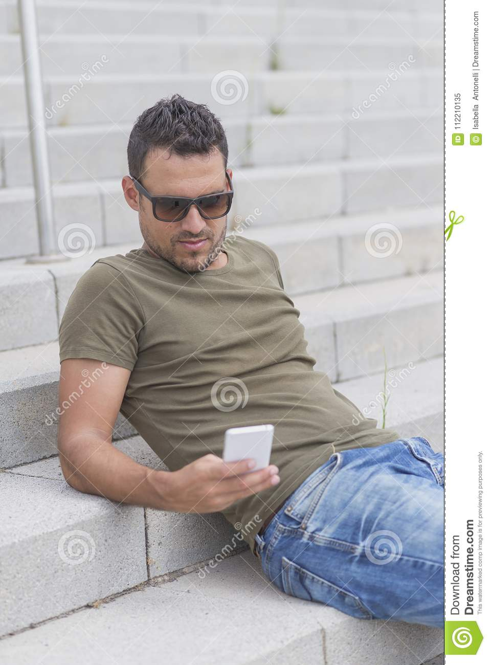 Outdoor portrait of modern young guy with mobile in the street s