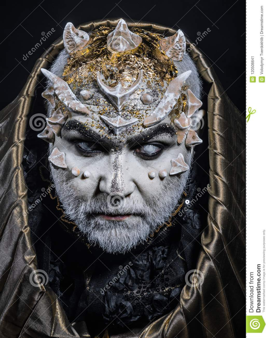 Man with thorns or warts, face covered with glitters. Demon with golden hood on black background. Senior man with white