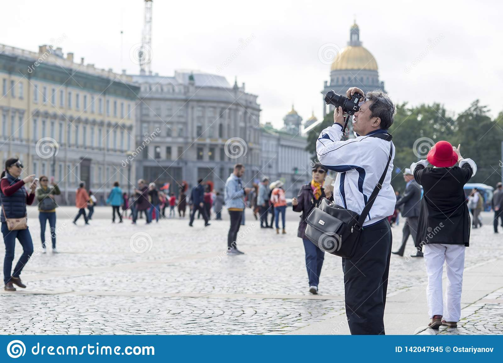 Man tourist Asian appearance photographs on camera attractions on the Palace square of St. Petersburg, Russia, September 2018.