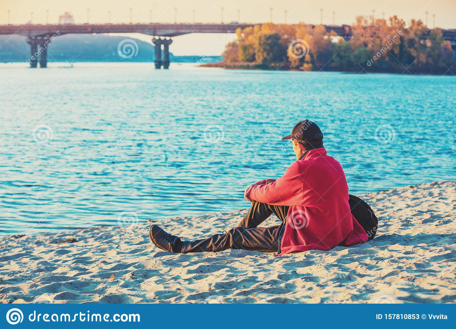 man-tourist-sitting-river-bank-autumn-looking-water-man-tourist-sitting-river-bank-157810853.jpg