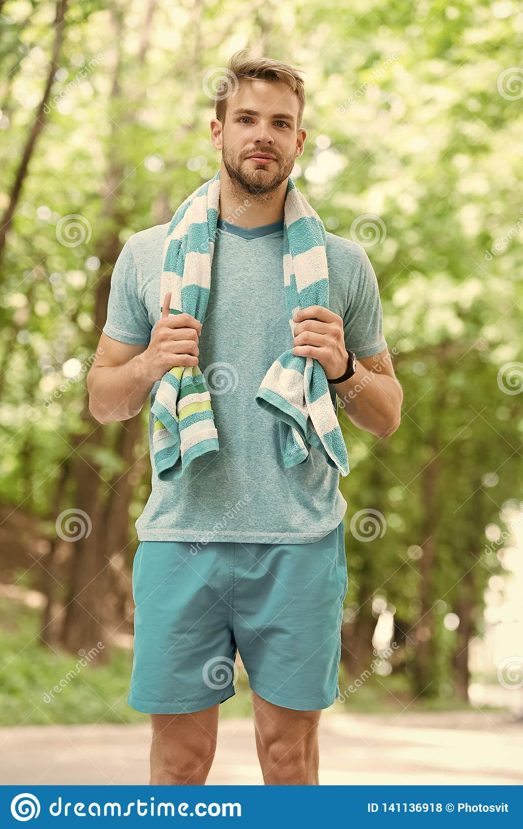 Man with towel on natural landscape. Sportsman just after training. Sweaty and tired. Summer beach time and vacation
