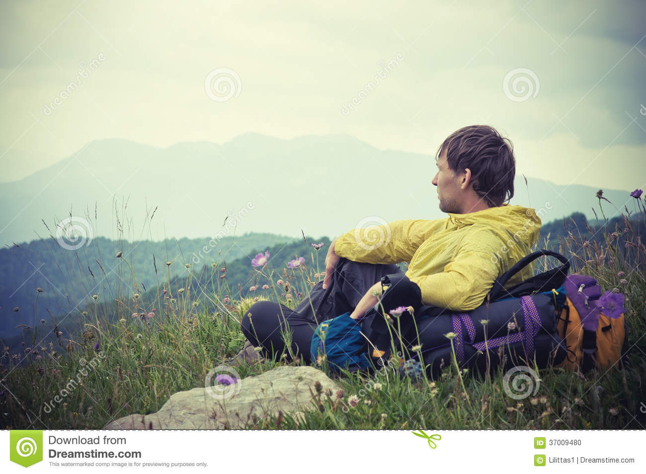 Man Traveler with backpack relaxing with Mountains on Background