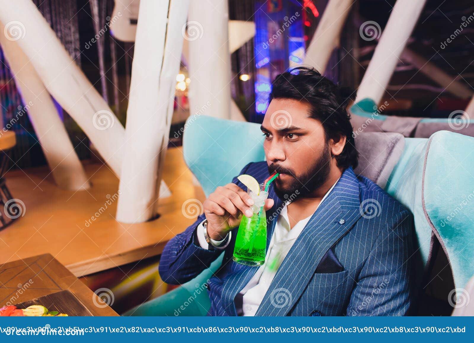 Man tv? i st?ngh?llexponeringsglas Sit At Counter som dricker coctailen, gladlynta v?nner som m?ter st?ngen, meddelar samtal