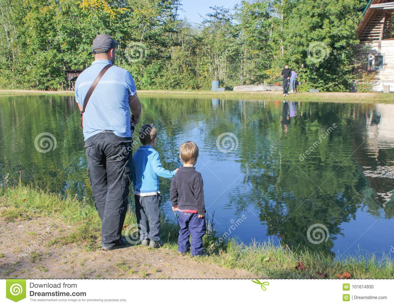 a man and two children fishing. Father and two sons fishing, trout at a trout farm. Children watch as fish..