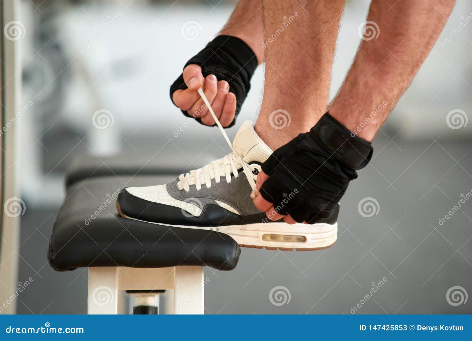 Man Tying Running Shoes In Gym. Stock