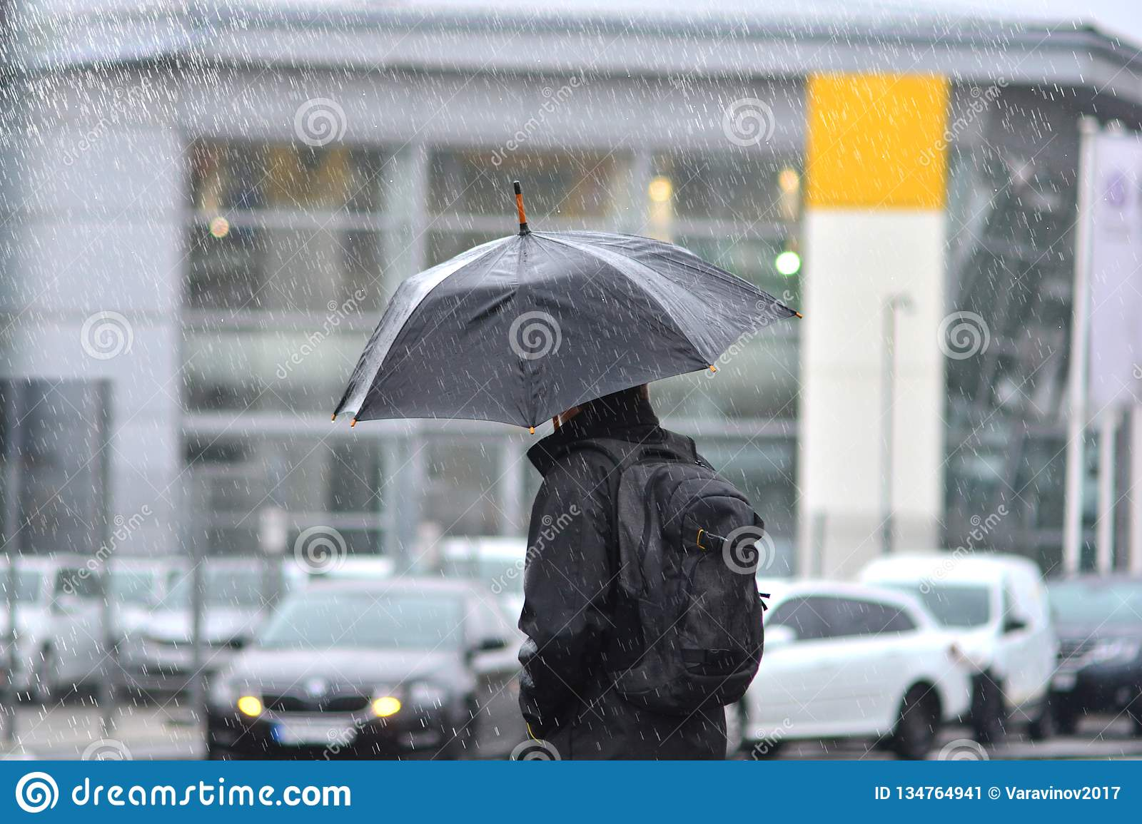 A man with an umbrella in the rain crossing the road.