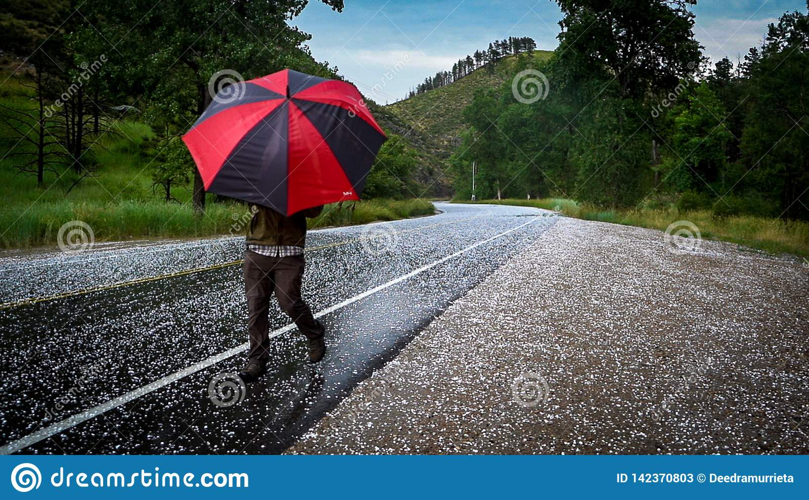 Man with umbrella on road with hail