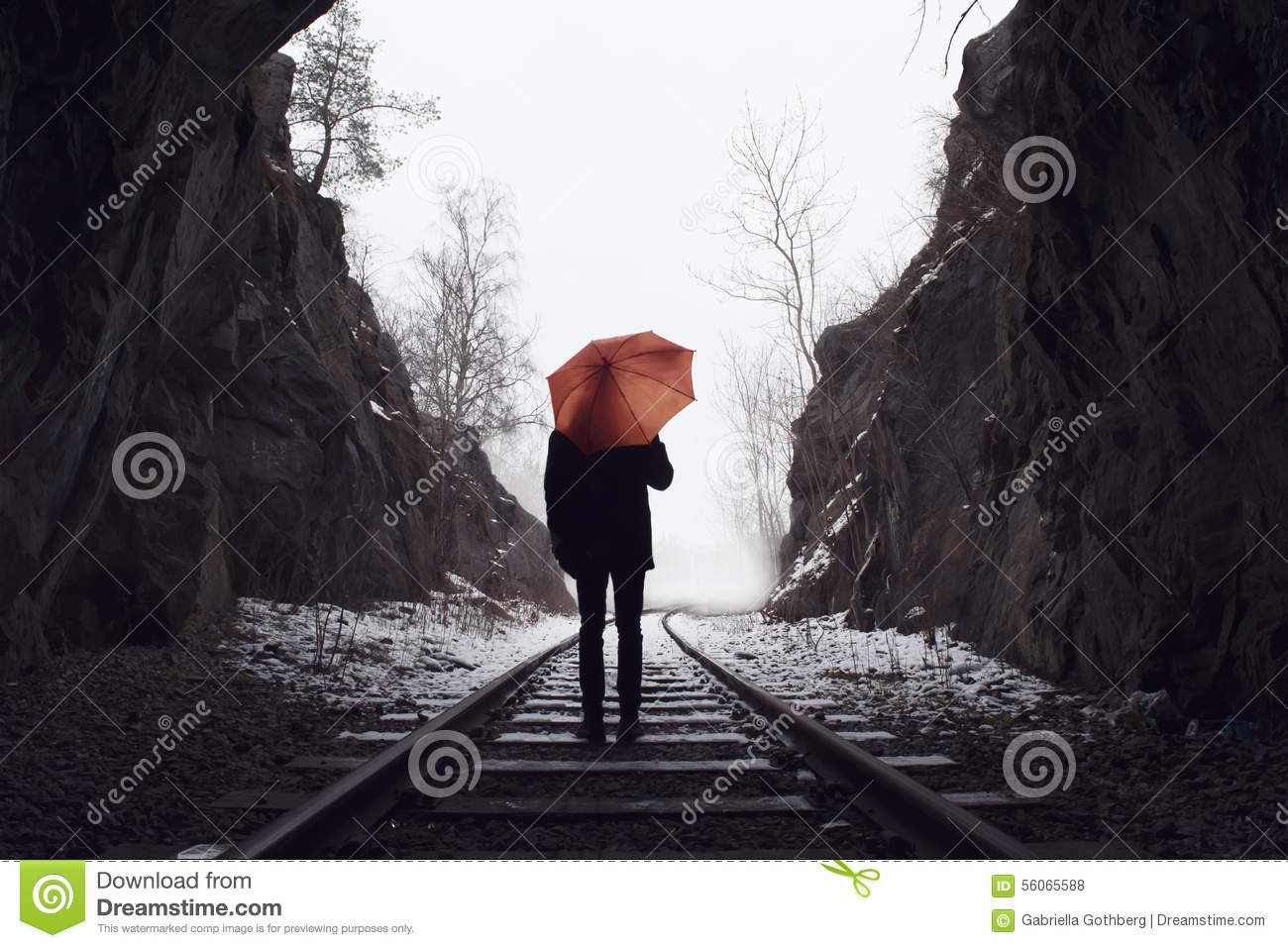 Man with umbrella standing on old railroad tracks vanishing