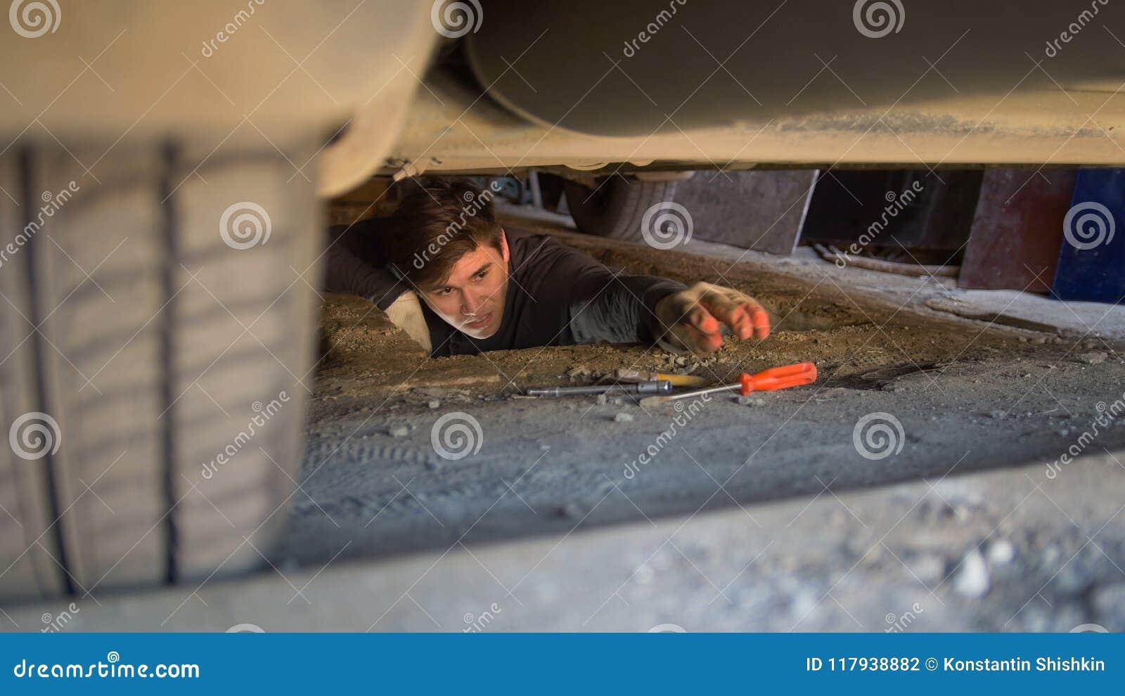 Man under en bil som når för en skruvmejsel för att reparera bilen
