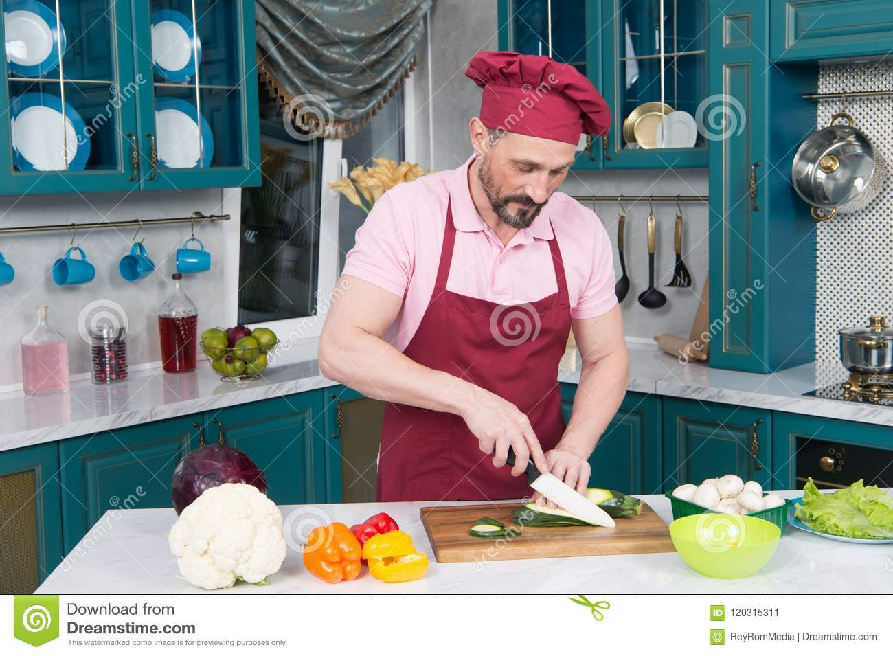 Man in uniform apron cutting zucchini on slice by knife. Orange and red paprika on table prepared for cutting after green zucchini