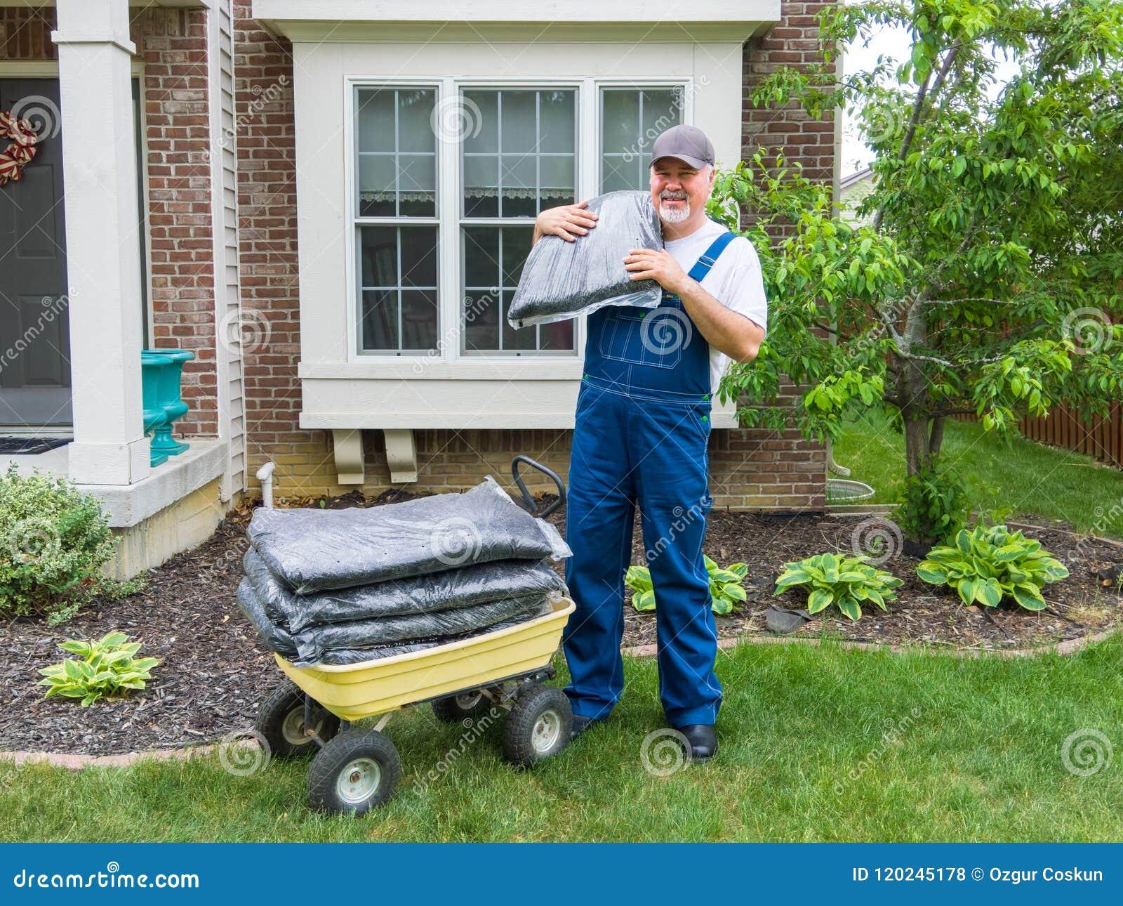Man unloading bags of mulch from a wheelbarrow