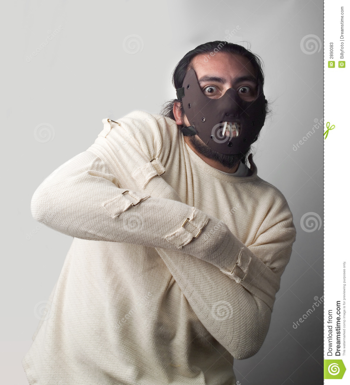 Man strapped up in a strait jacket with mask on his face.
