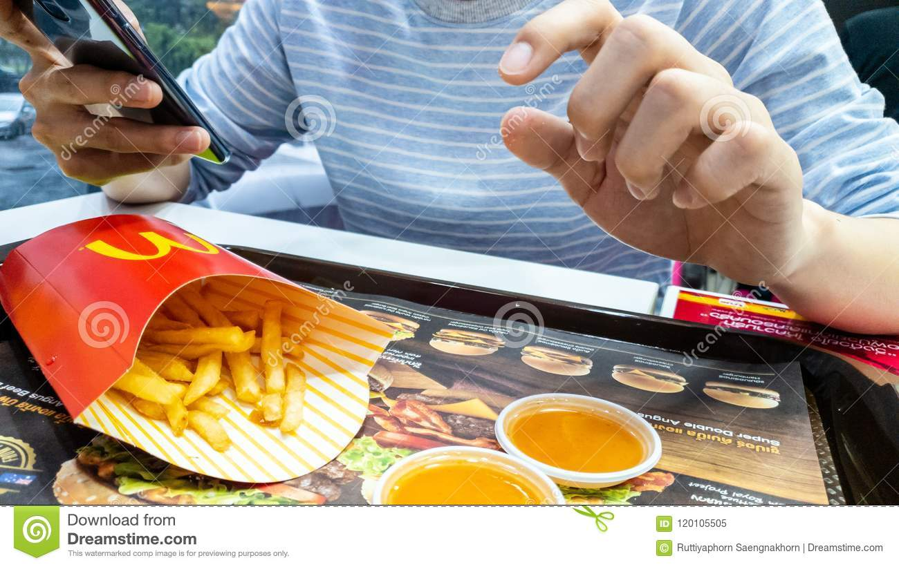 a man use smart phone and eating french fries container in red package and chili sauce on advertising paper at McDonald`s cafe