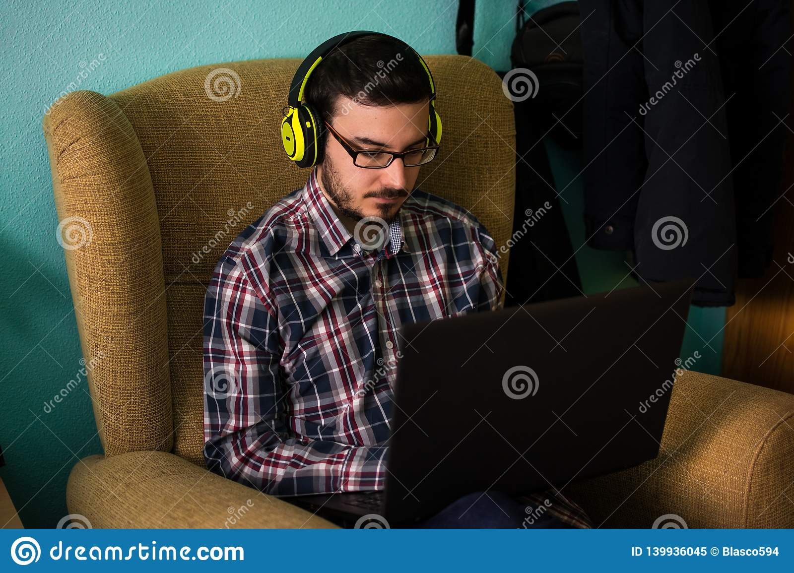 Man uses laptop on sofa in his home