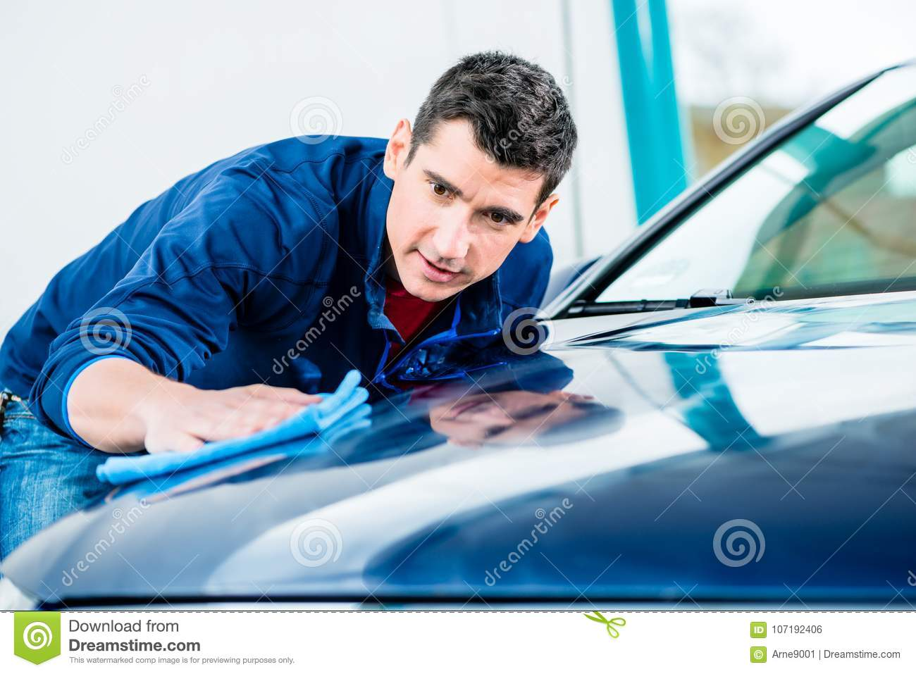 Man using an absorbent towel for drying the surface of a car