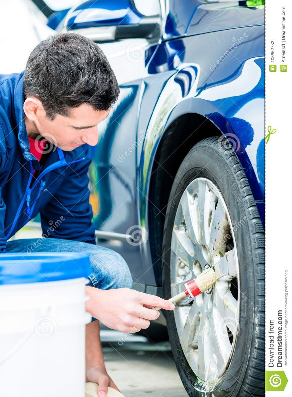 Man using brush for cleaning the surface of the rim