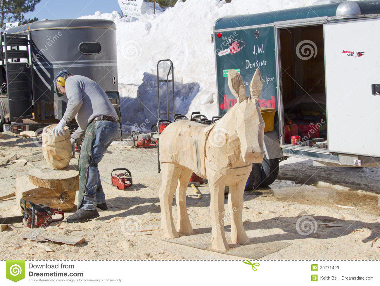 Man using chainsaw to carve a donkey wood carving