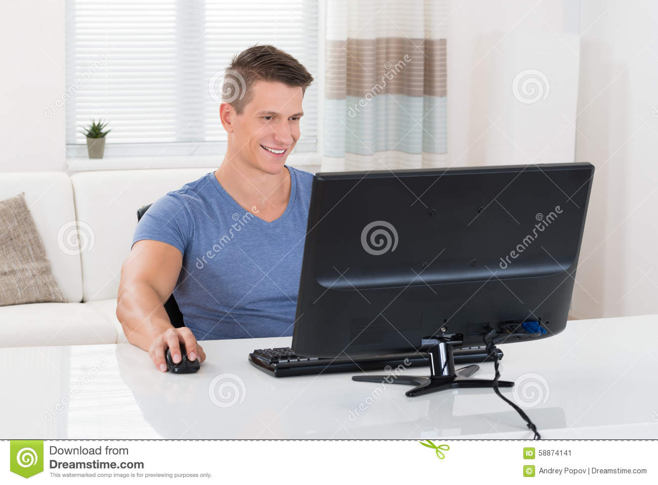 man-using-desktop-computer-young-happy-living-room-58874141.jpg