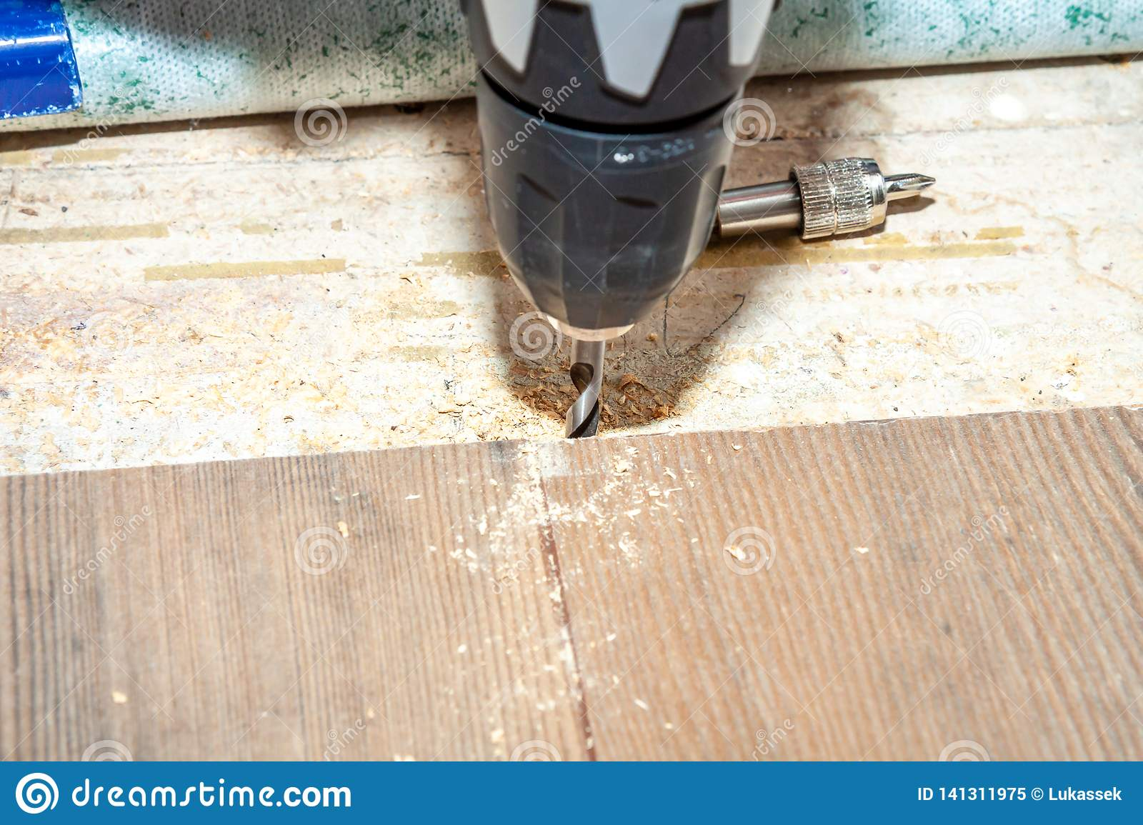 Man using drill machine while installing new wooden laminate flooring at home.