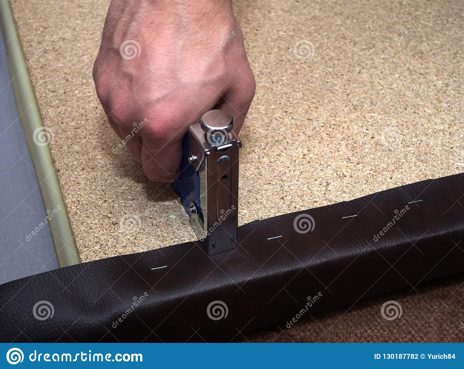 Man using hand-tool stapler and leatherette upholstering particle board