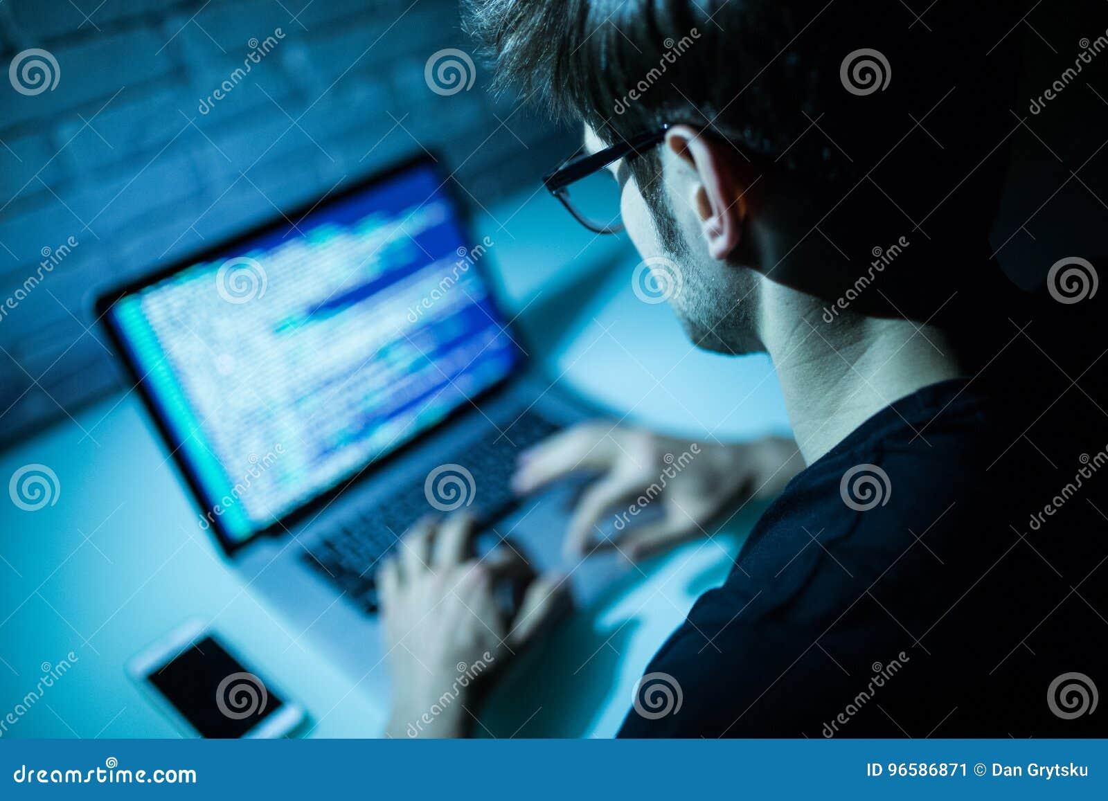 Man using laptop writing programming code on laptop. Young hacker work on laptop in the night
