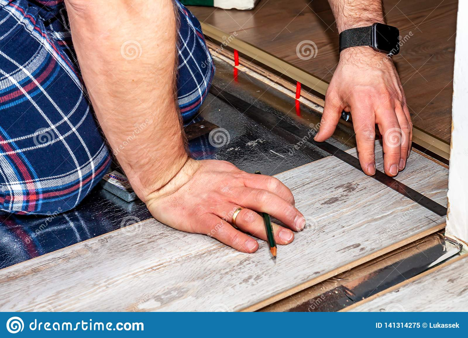 Man using measuring elbow and pencil while installing new wooden laminate flooring at home.