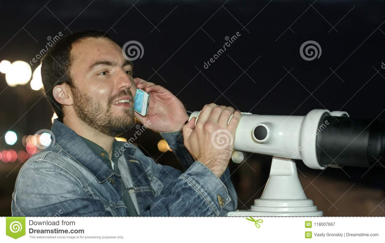 Man Using Mobile Phone And Looking Into A Tower Viewer ...