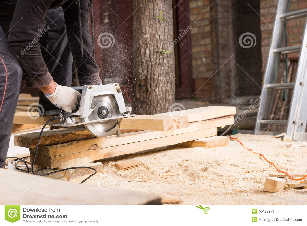 Man Using Power Saw To Cut Planks Of Wood Stock Photo