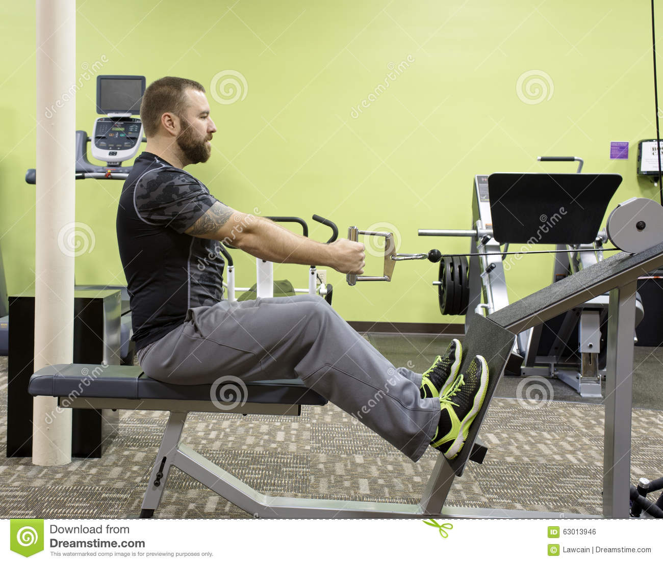 Man Using Seated Row Machine Stock Photo - Image: 63013946