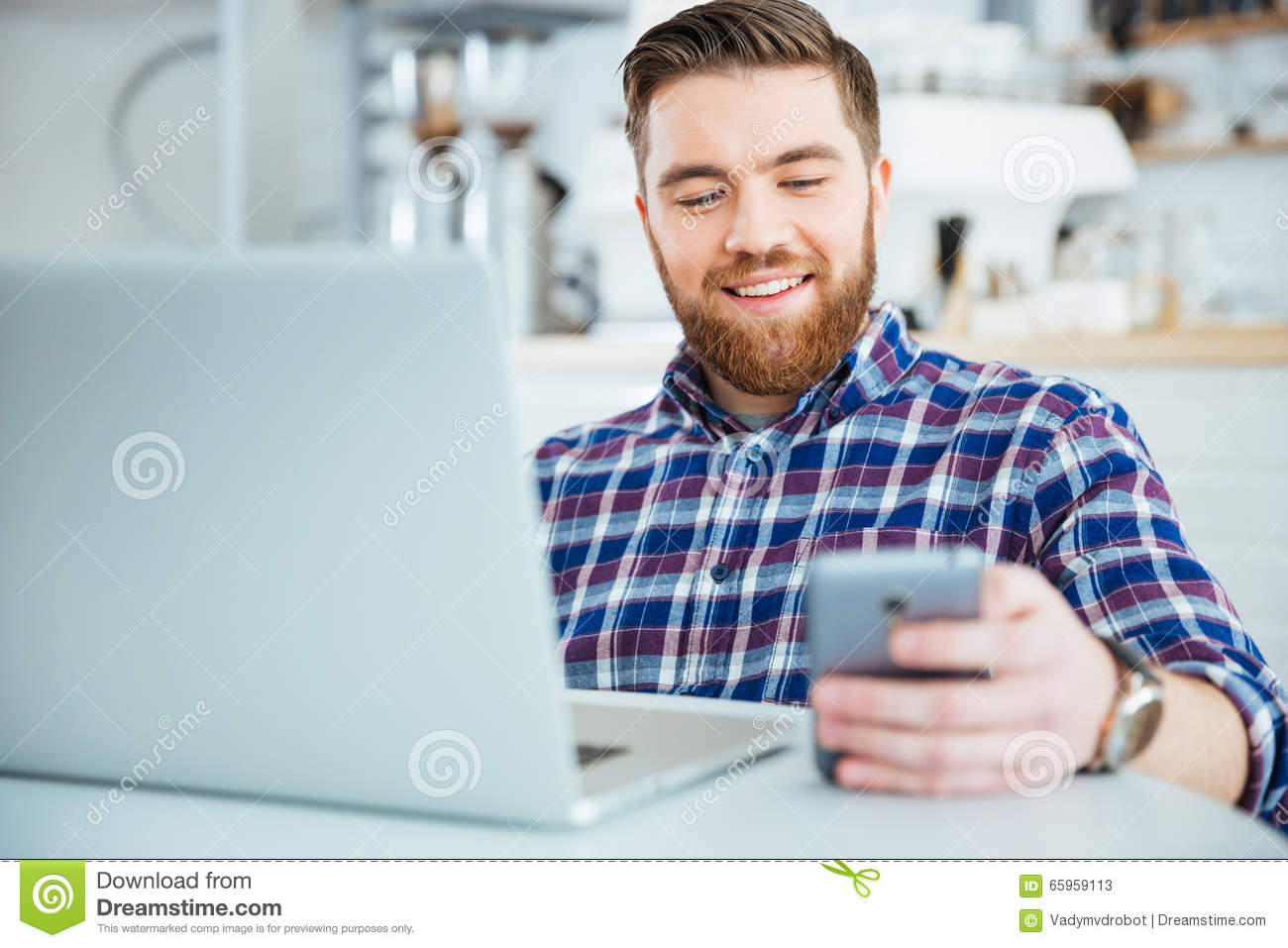 Man using smartphone and laptop compute in cafe