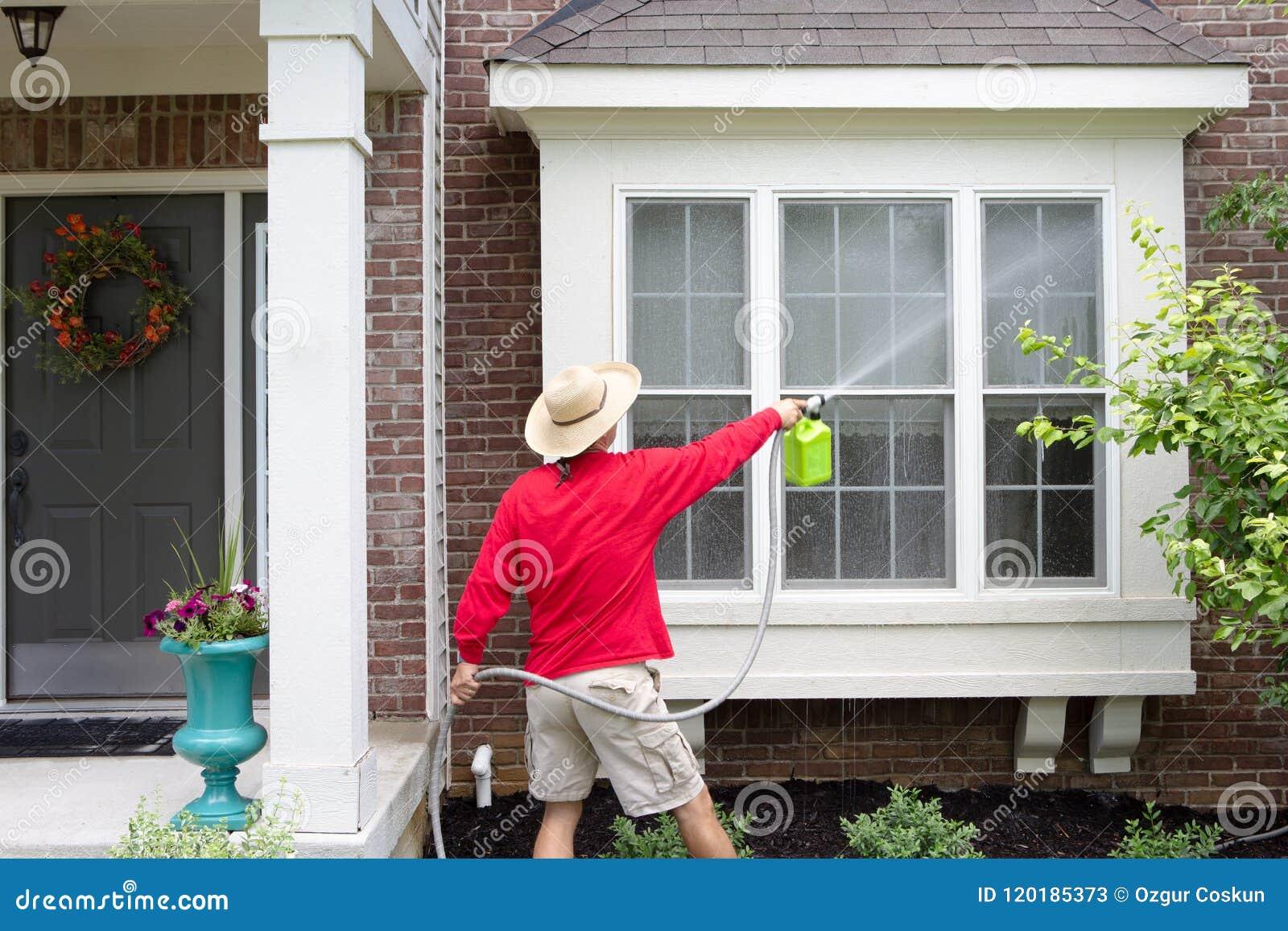 Man våren som gör ren yttersidan av hans hus