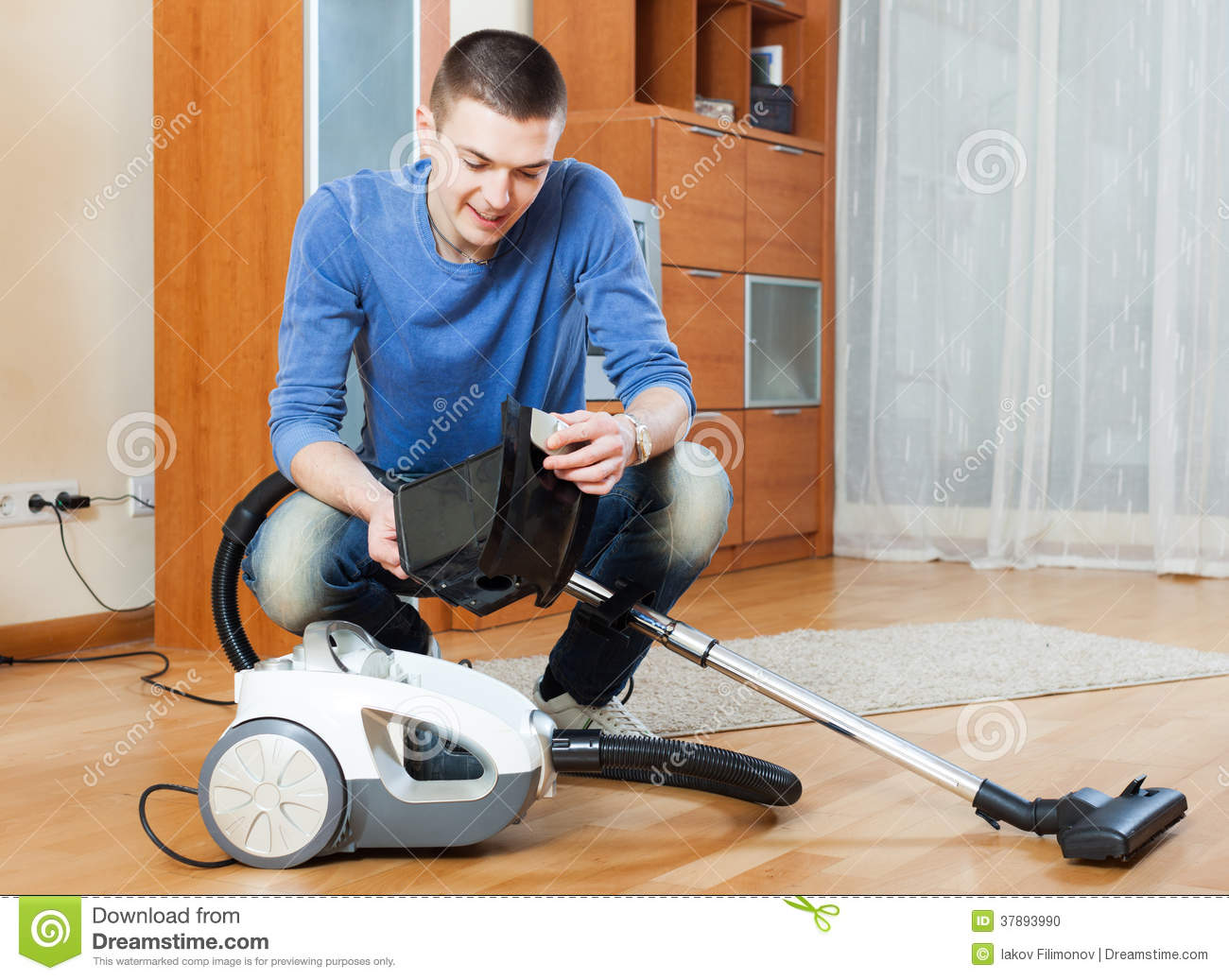Man Vacuuming With Vacuum Cleaner On Parquet Floor In